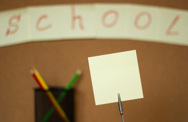 """Stickers and colored pencils on a blurred background of a cork board with an inscription """"school"""", copy space"""