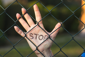 Female hand with Stop sign behind a fence. Stop - here is a border!