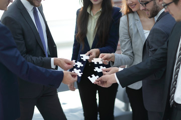 Group of business people assembling jigsaw puzzle, team support