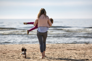 young blode woman mother is playing with a girl daughter and yorkshire dog puppy in summer spring at the beach