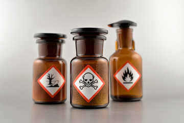 Vial with warning pictogram stock images. Laboratory accessories. Vials on a silver background. Brown glass containers. Brown chemical glass
