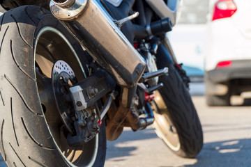 Rear view of motorcycle. Rear wheel, exhaust pipe. Soft focus, blurred background.