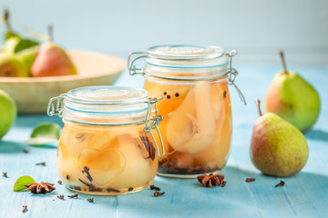 Natural and juicy pickled pears on blue table