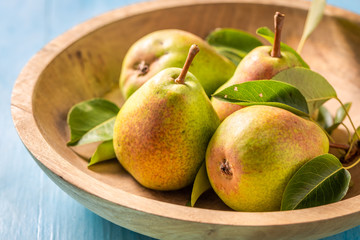 Juicy pears on the wooden bowl and blue table