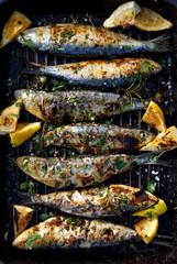 Gegrilde sardines in een kruiden-citroenmarinade op een grillplaat, bovenaanzicht. Gegrilde zeevruchten, barbecue