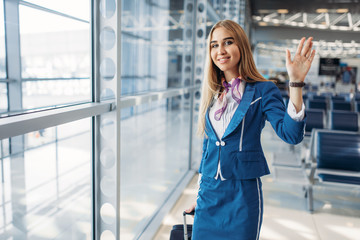 Stewardess with suitcase wave her hands in airport