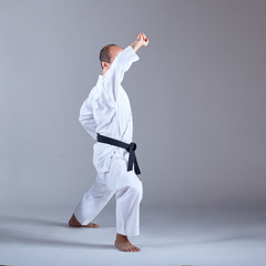 With a black belt, the athlete trains the block with his hand in a formal karate exercise