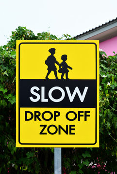 slow down drop off zone warning yellow banner traffic sign at the school