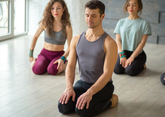 Positive athletic male Instructor taking yoga class in fitness studio with grey background performing asana with fit women pupils on background. Active leisuretime and Healthy Activities.