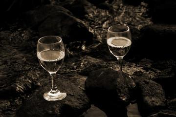 Weißweingläser auf Steinen im fließenden Wasser