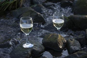 Weißweingläser bei Morgenlicht in fließenden Gewässer