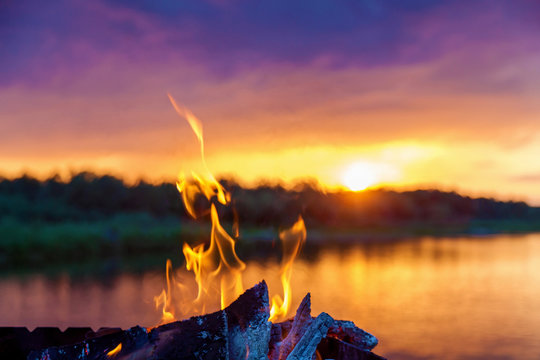 bonfire by the river at sunset