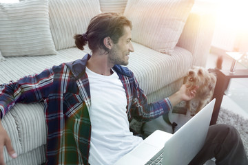 stylish young man stroking his pet and working on laptop