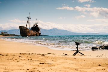 Camera on tripod and shipwreck