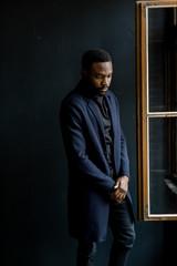 Studio shot of young handsome African businessman wearing coat on dark background.