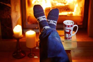 Man's feet in warm socks with large mug of hot chocolate and murshmallows near fireplace