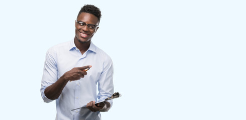 Young african american man holding a clipboarad pointing with hand and finger up with happy face smiling