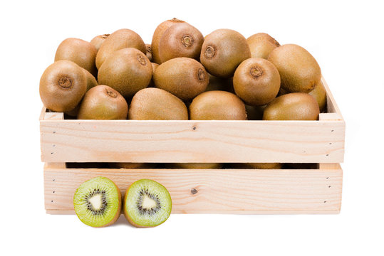 Wooden box filled with many ripe and fresh kiwi fruits and two half fruits in front of it isolated on white background