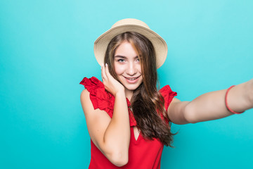 Young beauty woman in straw hat take sefie on blue background
