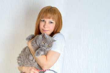 Blond / red hair mature senior female relaxing at home holding and hugging cute purring  cat. Attractive middle aged woman with big british shorthair cat resting at home.A woman in period of menopause