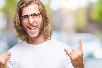 Young handsome man with long hair wearing glasses over isolated background shouting with crazy expression doing rock symbol with hands up. Music star. Heavy concept.