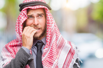 Young handsome arabian man with long hair wearing keffiyeh over isolated background looking stressed and nervous with hands on mouth biting nails. Anxiety problem.