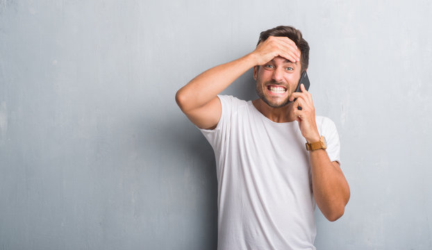 Handsome young man over grey grunge wall speaking on the phone stressed with hand on head, shocked with shame and surprise face, angry and frustrated. Fear and upset for mistake.