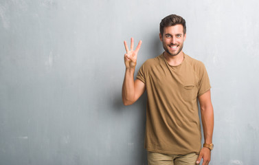 Handsome young man over grey grunge wall showing and pointing up with fingers number three while smiling confident and happy. Wall mural