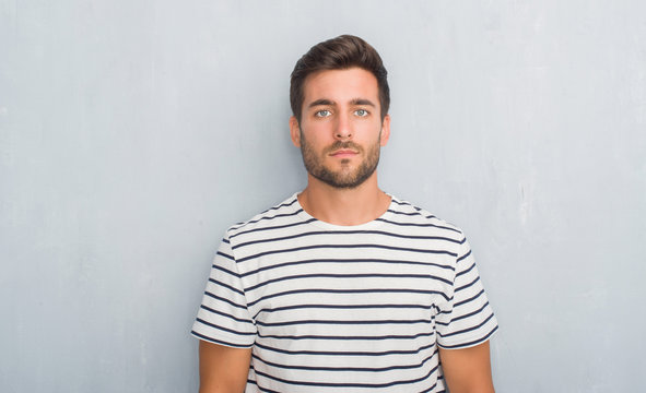 Handsome young man over grey grunge wall wearing navy t-shirt with serious expression on face. Simple and natural looking at the camera.