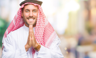 Young handsome man wearing keffiyeh over isolated background praying with hands together asking for forgiveness smiling confident.