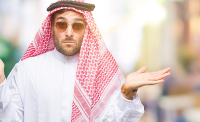 Young handsome man wearing keffiyeh over isolated background clueless and confused expression with arms and hands raised. Doubt concept.