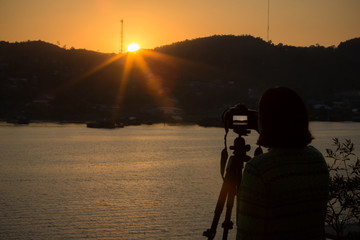 Photographer taking  travel nature photography. Woman photographer shooting with tripod and DSLR camera in sunset with beautiful landscape in background.