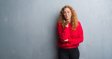 Young redhead woman over grey grunge wall wearing red sweater looking at the camera blowing a kiss with hand on air being lovely and sexy. Love expression.