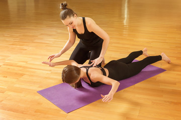 Pilates trainer is teaching young healthy woman at gym. Fitness exercise workout.