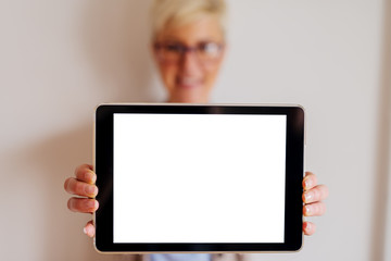 Close up of focus view of tablet with white editable screen . Blurred picture of a woman standing behind tablet and holding it.