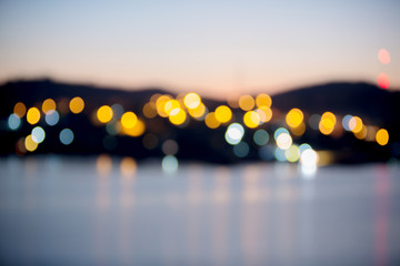 Blurry bokeh light of the riverside town in twilight time. beautiful cityscape at night. image for background, walllpaper and copy space.