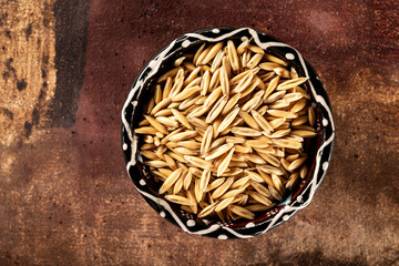 Top view image of a bowl with uncooked crude oats at brown stone background.