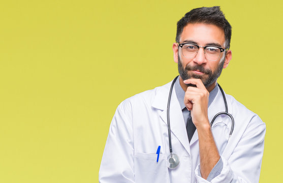 Adult hispanic doctor man over isolated background looking confident at the camera with smile with crossed arms and hand raised on chin. Thinking positive.