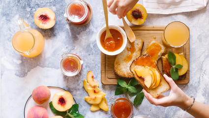 Toasts of bread with apricot jam and fresh fruits with leaves on white wooden table. Tasty breakfast.