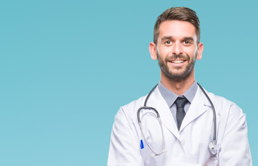 Young handsome doctor man over isolated background happy face smiling with crossed arms looking at the camera. Positive person. Wall mural