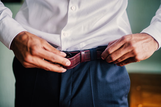 Close up of mans hands putting belt on his pants.