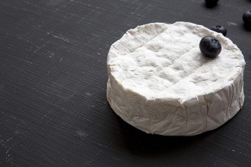 Camembert cheese with blueberries on dark surface, side view. Food for romantic. Copy space.