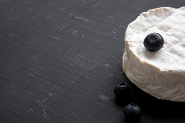 Camembert cheese with blueberries on dark background, side view. Food for wine. Space for text.