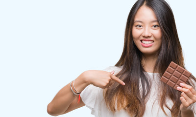 Young asian woman eating chocolate bar over isolated background with surprise face pointing finger to himself