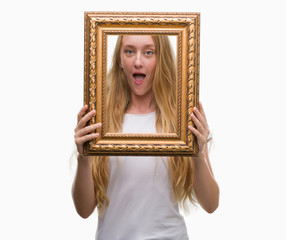Blonde teenager woman holding vintage frame art scared in shock with a surprise face, afraid and excited with fear expression