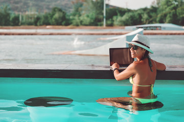 Young slim woman freelancer in bikini, straw hat and sunglasses works with laptop notebook sits in swimming pool