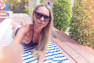 Young pretty blonde woman with smartphone taking selfie photo or speak by video chat