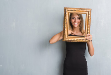 Beautiful young woman over grunge grey wall holding vintage frame with surprise face pointing finger to himself