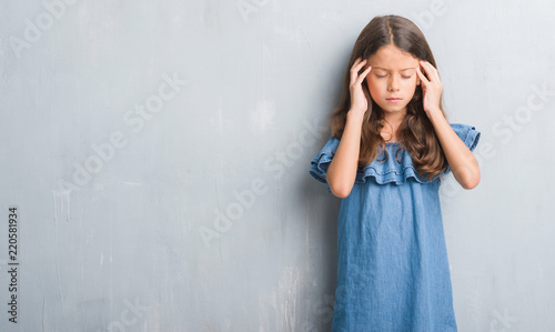 942a172418f4 Young hispanic kid over grunge grey wall with hand on head for pain ...