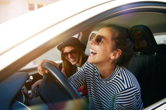 Carefree young friends driving together in a car laughing